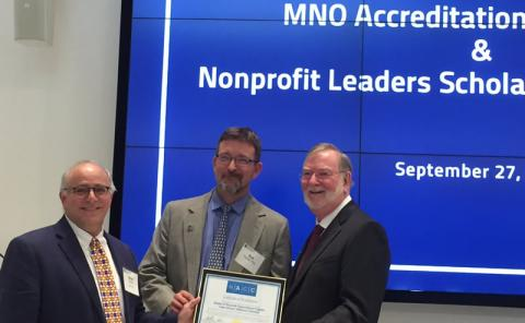 Stuart C. Mendel, Ph.D. presents NACC accreditation to MNO Program Chair Robert L. Fischer, Ph.D., and Dean Grover C. Gilmore, Ph.D.